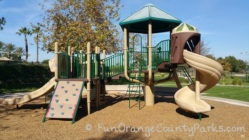 another view of the same playground where you can see a twisty slide and climbing board with grips