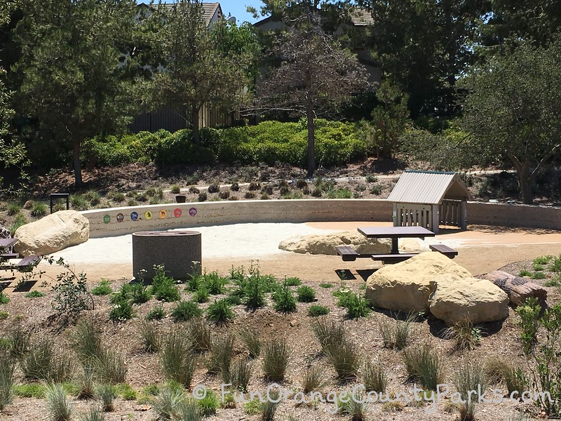 picnic table and native plants surrounding sand play area