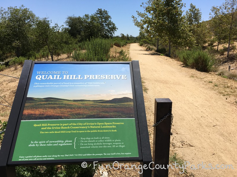 Quail Hill Preserve trail sign on left with dirt trail heading off in the distance on the right