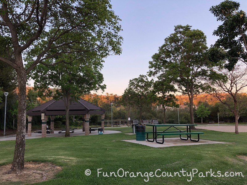 covered picnic shelter and open air picnic table on a grassy area with trees at Ronald Reagan Park in Anaheim Hills