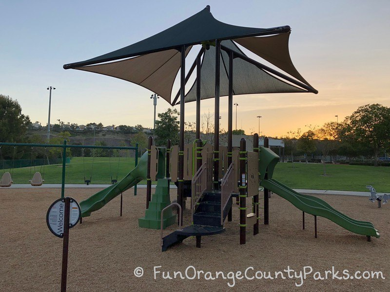 brown and green play structure with shade sails and a grassy area in the background