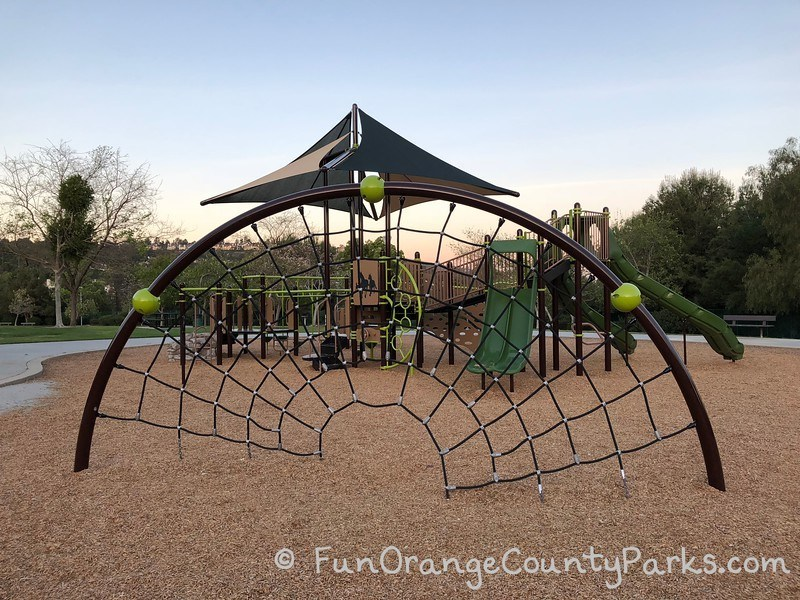 half circle arch on a bark play surface with black rope netting for climbing - playground in back