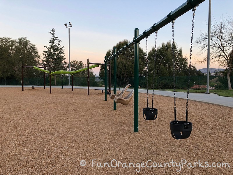 2 baby swings, 2 accessible swings, 2 bench swings, and a zip track on a bark play surface at Ronald Reagan Park in Anaheim Hills