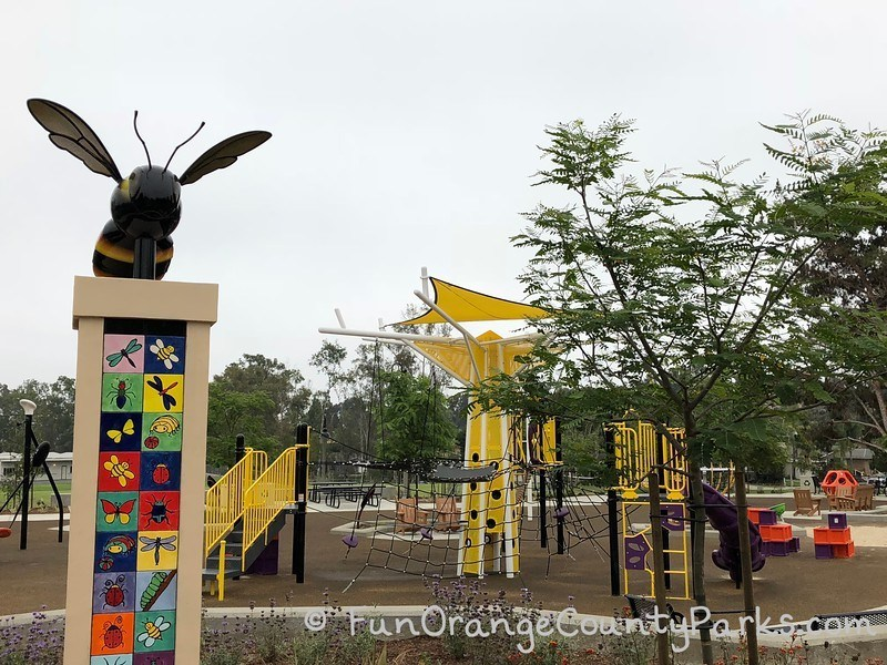 bumble bee sculpture on top of a colorful tiled pedestal with the bright yellow playground in the background