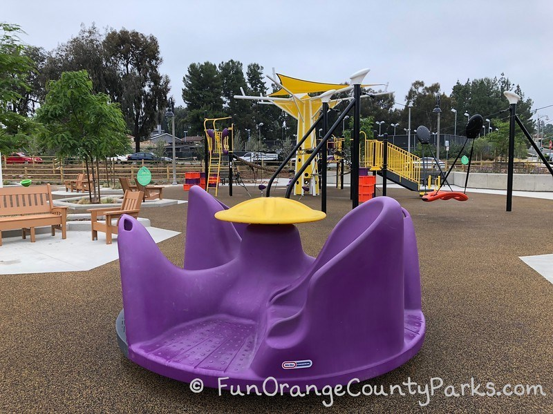 plastic purple merry-go-round at Cordova Park in Mission Viejo with playground in view behind it