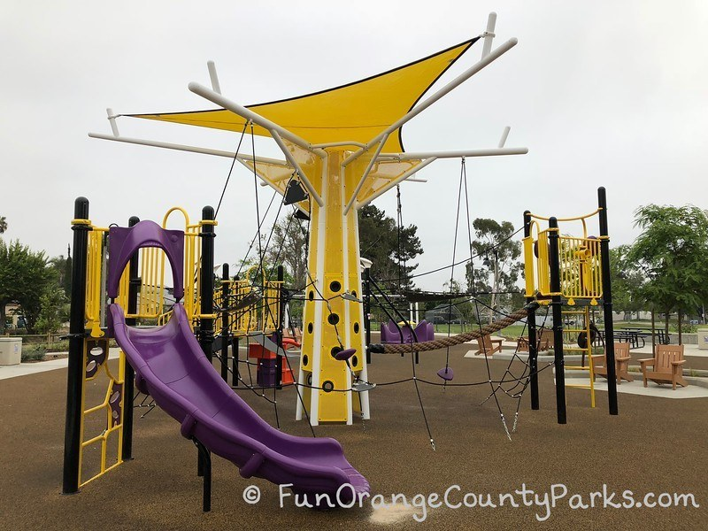 purple slide and views of the black rope netting and climbing opportunities on a brown recycled rubber surface that runs throughout Cordova Park playground