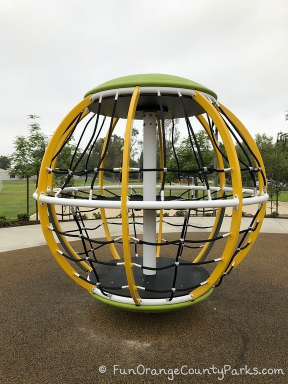 large yellow globe-shaped equipment with black netting tall enough for kids to stand inside while it spins