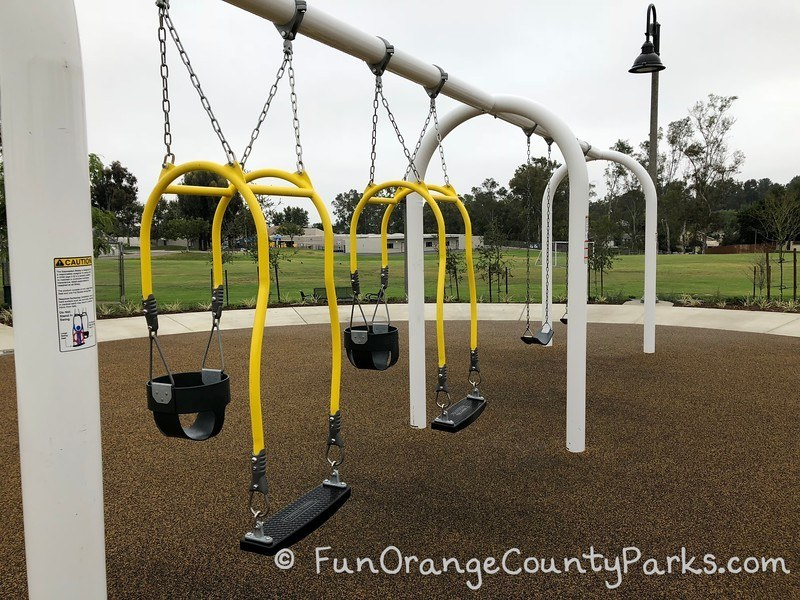 2 mommy and me swings with 2 bench swings above brown recycled rubber surface with grass field and school buildings behind the swings