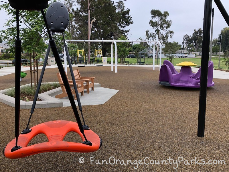 orange swing and purple spinner with layout of Cordova Park playground more visible