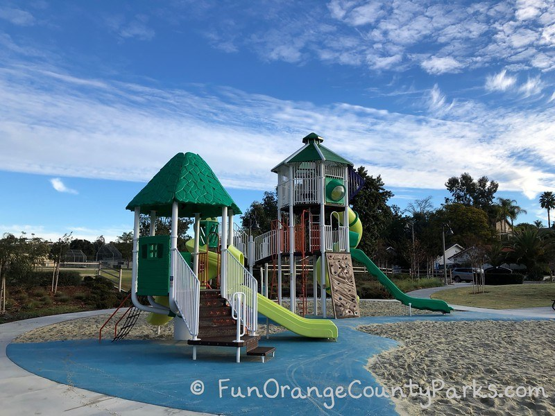 smaller playground area with toddler size slide and big blue sky as background
