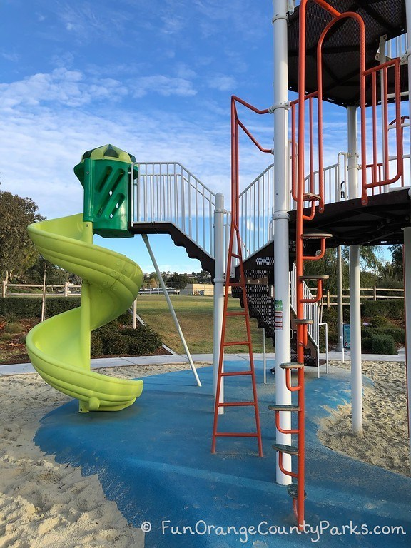 neon green twisty playground slide and ladders