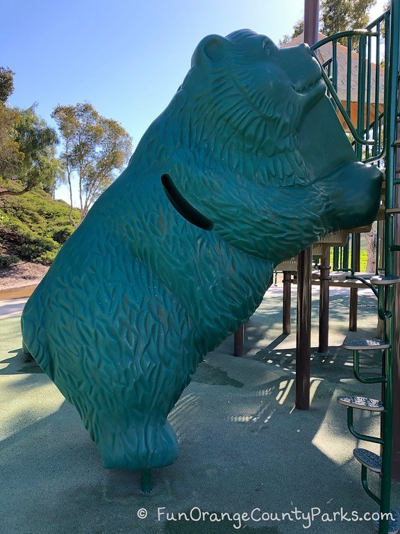 bear climber in green plastic that looks like a giant bear is leaning on the playground equipment -- with a way to climb up inside