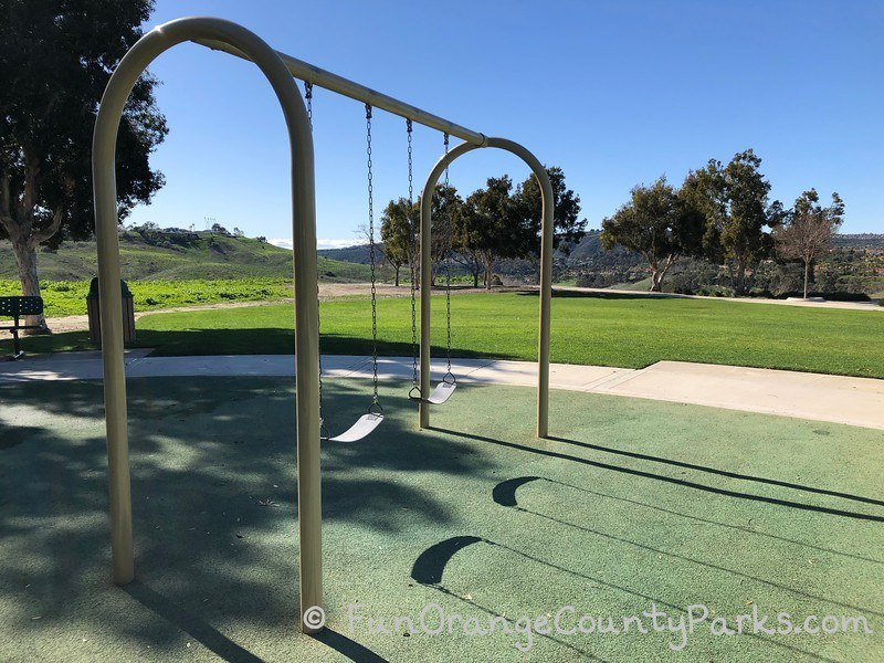 bench swings over a recycled rubber surface near a grassy area