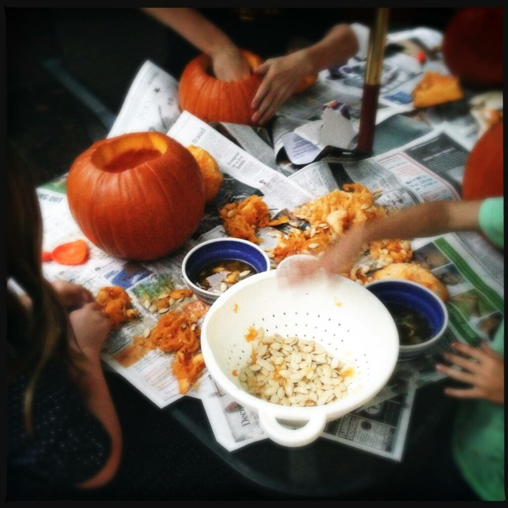 school age children carving October Halloween pumpkins with bowls of pumpkin seeds on newspaper