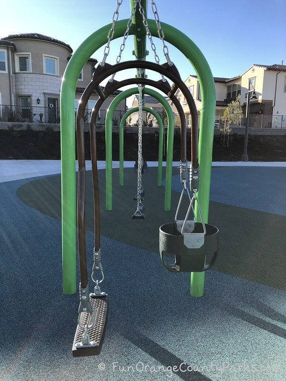 bank of five swings with green arches
