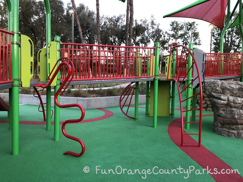 cherry park lake forest playground with red bridge and 4 different ladders visible on a green recycled rubber play surface
