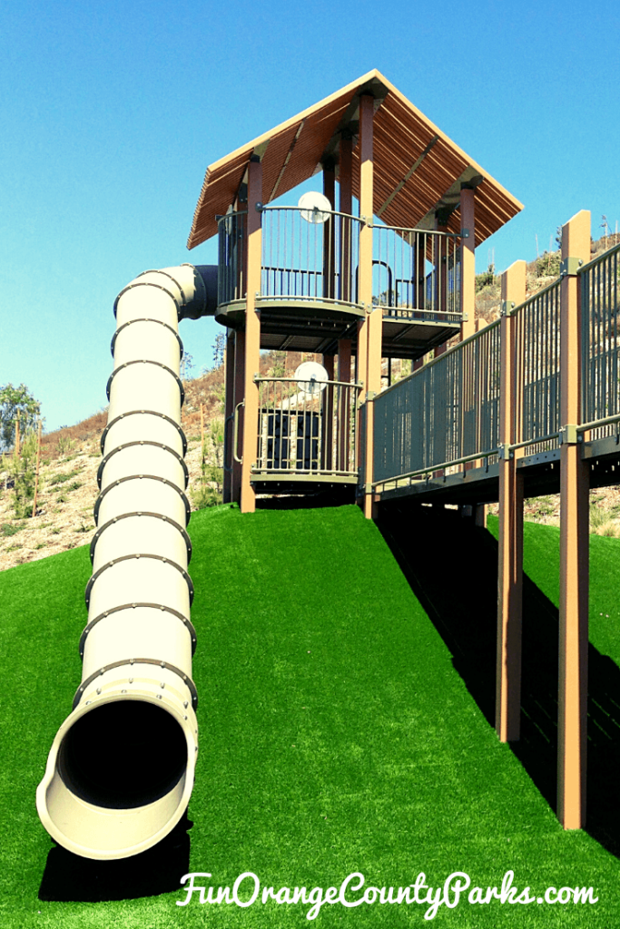 green astroturf hill topped with what looks like a treehouse playground and an enormous beige tunnel slide coming off the tower