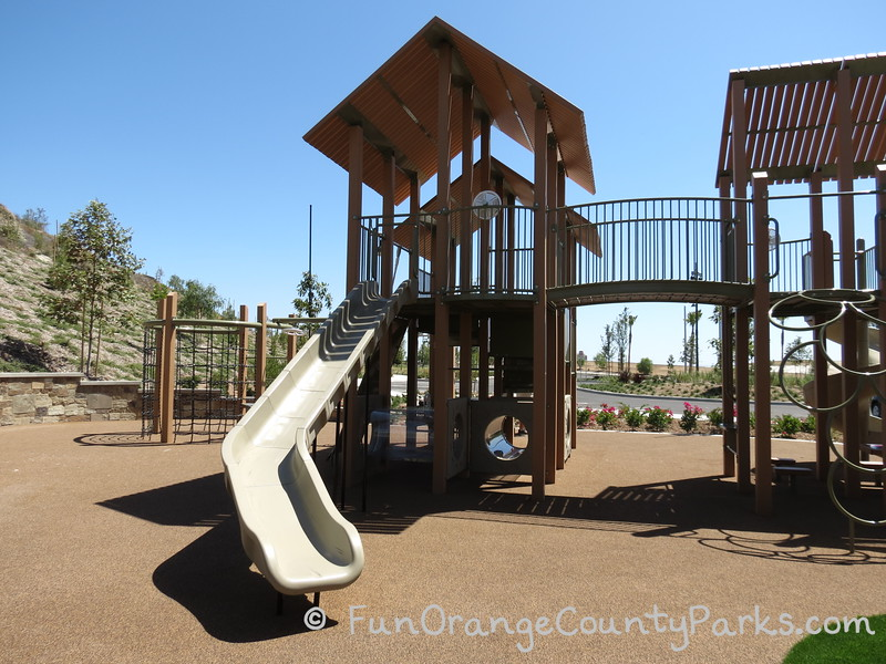 View of the monkey bars at Baker Ranch Community Park with a crooked slide  and climbing apparatus
