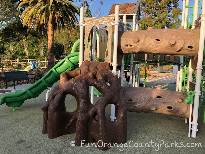 two tree tunnels and tree root climber on playground with neon green slide leading off the left side of the photo