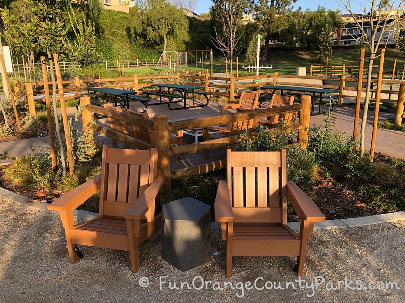 3 green metal picnic tables inside a fenced picnic area with two adirondack chairs and a side table for lounging - lawn area and play equipment in the background.