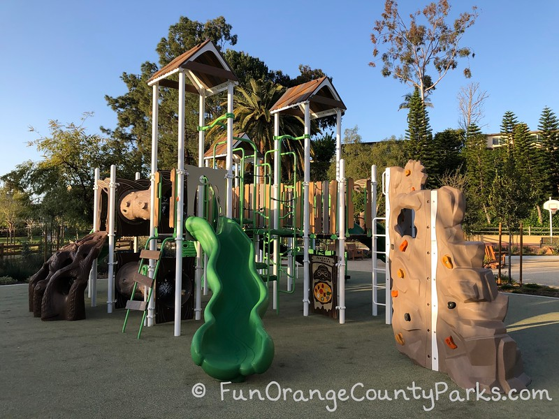 main playground with green slide and a climbing wall