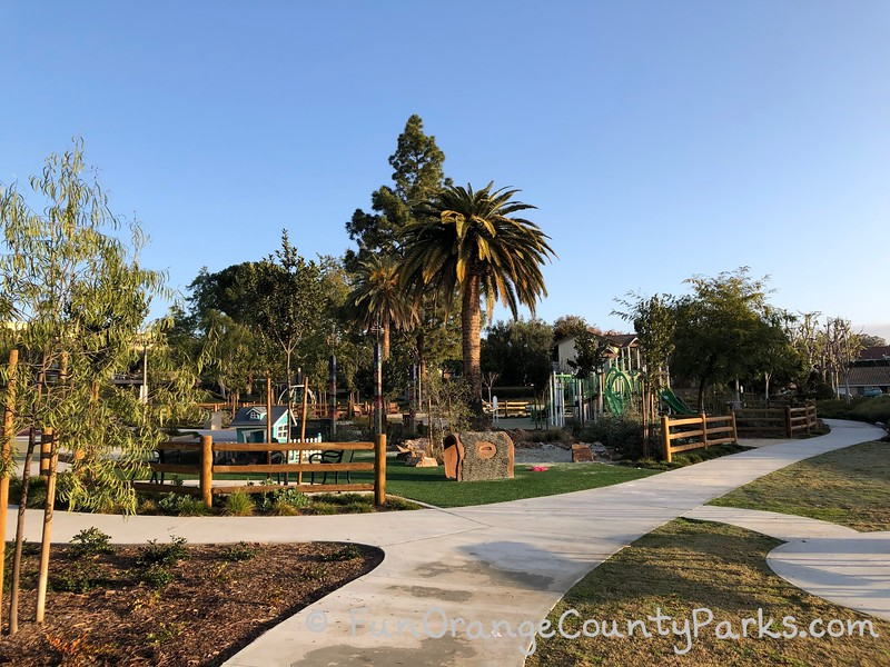 sidewalk into christopher park in mission viejo with big palm trees in the center of the playground. small play house and playground visible through the trees.