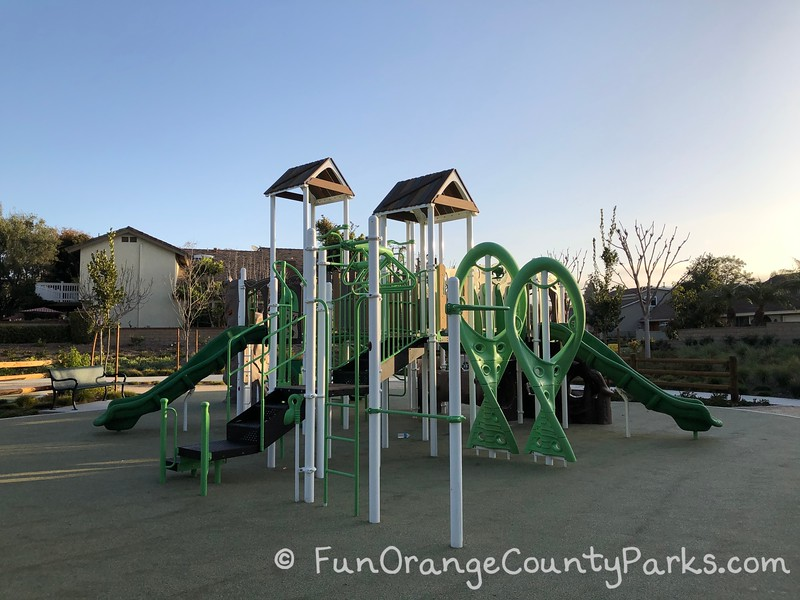 neon green playground with monkey bars and slides coming off either end on recycled rubber play surface at christopher park in mission viejo