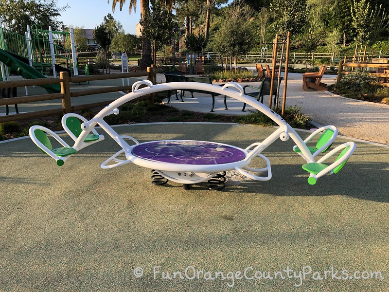 4 person teeter totter with neon green seats and a purple pad in the center