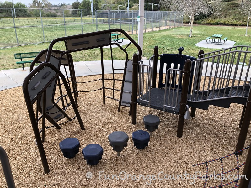 pedestals and clmibing apparatus on the playground at Fullerton Sports Complex with picnic tables and lawn area in the background