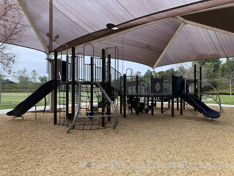 playground under shade cover with bark play surface and Fullerton Sports Complex playing fields in the background