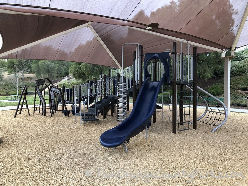 main playground with a navy blue slide and shiny metal corkscrew and stairs on a bark play surface under a brown shade cover