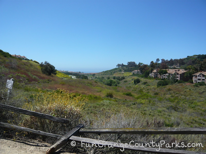 broken wooden fence with a canyon that has bushes and trees with ocean in distance and apartment buildings on the right