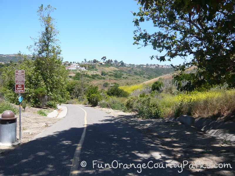 paved trail leading to Salt Creek Trail in Dana Point with brush and trees surrounding the trail
