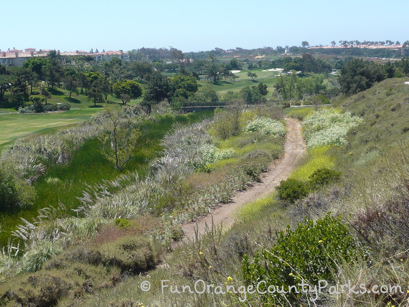 golf course and hotel view with creek slightly visible near a dirt trail
