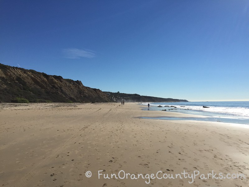 wide beach at Crystal Cove State Park which is almost empty except for a few people walking