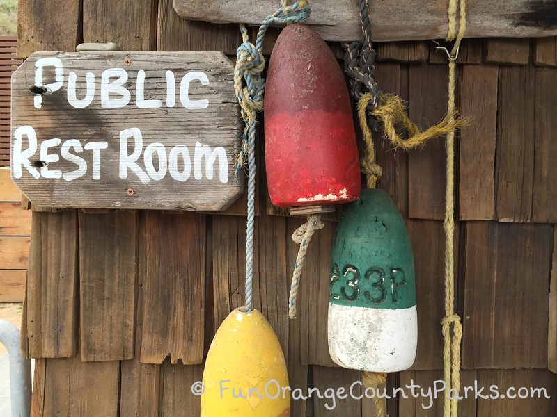 public restroom sign with colorful buoys hanging on a shingled wall