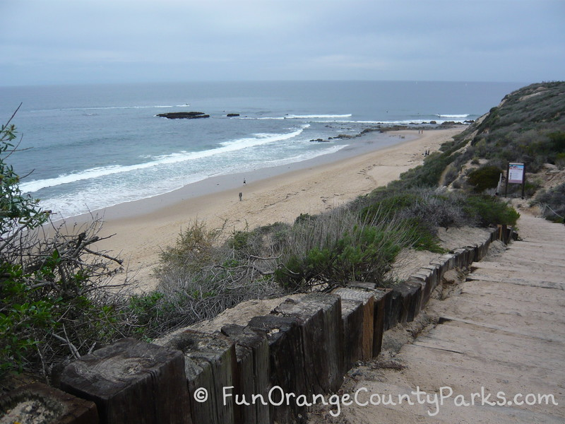 shoreline with obvious tidepools on a cloudy day with a wooden staircase leading down to the beach at Crystal Cove State Park