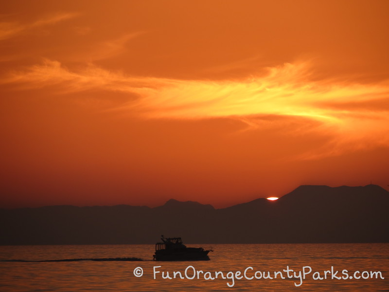 brilliant orange sunset view of catalina island with a boat on the ocean