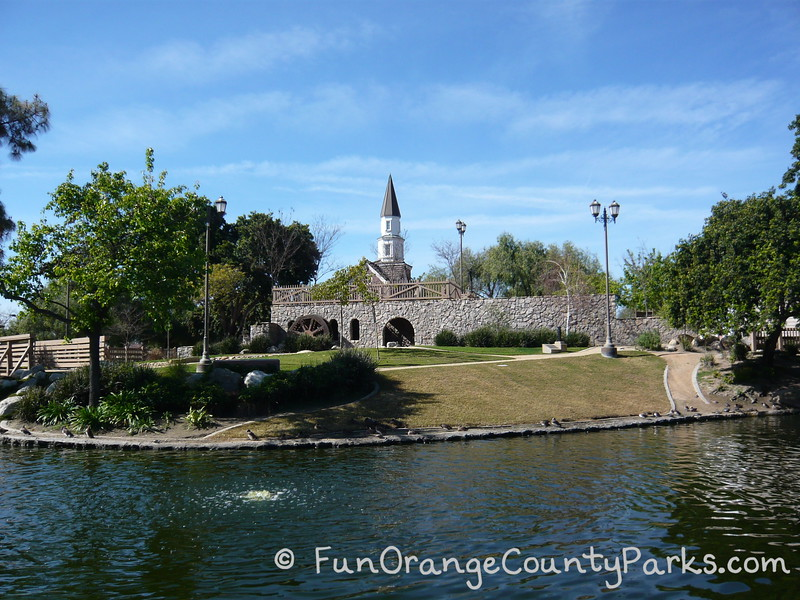 view across the moat of heritage park play island in cerritos where you can see the church tower and colonial style wall against a blue sky