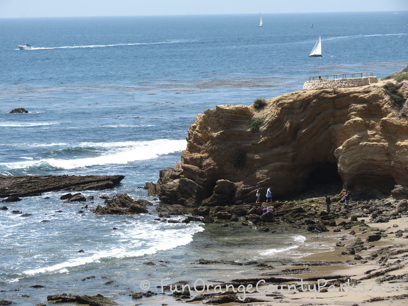 pelican point and treasure cove area of crystal cove state park with rock formation and people walking on tidepools