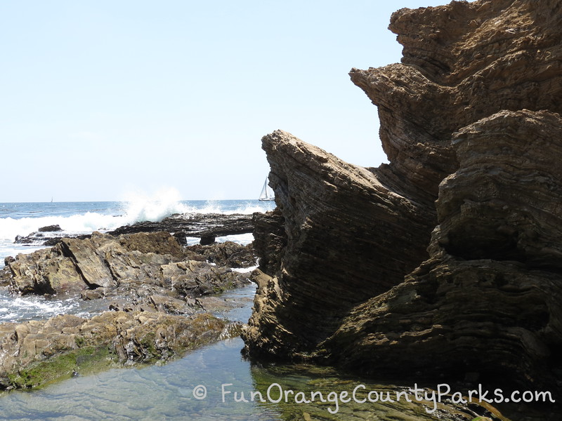 rocks that look layered with waves splashing over them and a sailboat in the distance