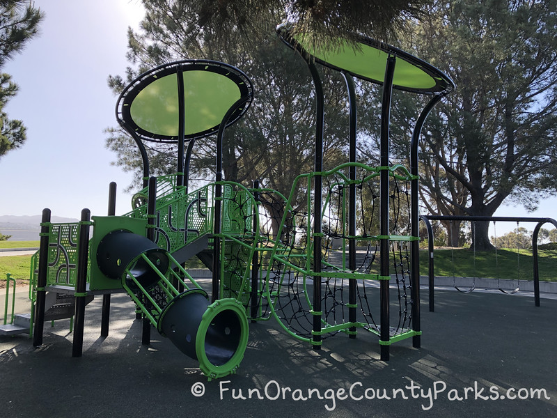 another view of the playground with 2 bench swings visible and close up of climbing area which has black netting for vertical and horizontal movement