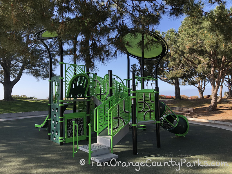 neon green and black playground with circular sun shades and modern feel surrounded by pine trees at Lantern Bay Park in Dana Point