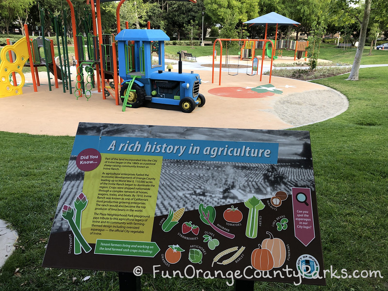"""Plaza Park sign about """"A rich history in agriculture"""" in the foreground with a blue tractor built into a play structure with 2 bench swings and another play structure visible"""