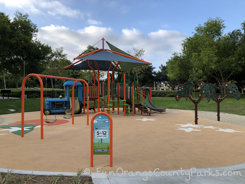 Plaza Park in Irvine 5-12 year old play area on a recycled rubber surface decorated with orange and orange blossoms with a swing set on the left and 2 orange tree climbers on the right. Central is play structure with blue tractor and shade sail.