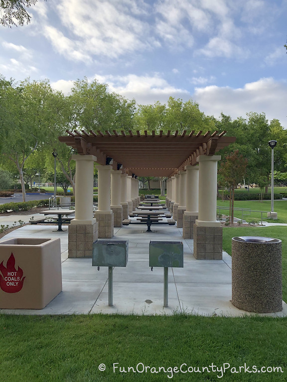 covered picnic area with lots of 4-person tables that have built-in benches. 2 grills, a hot coals bin and a trash bin at either end