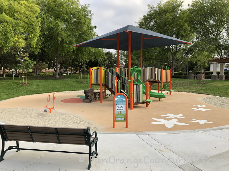 Plaza Park 2-5 year old play structure with view from the back of a bench towards the smaller play equipment with sand areas along the edges, an orange digger/excavator, and green slide under a blue shade sail.