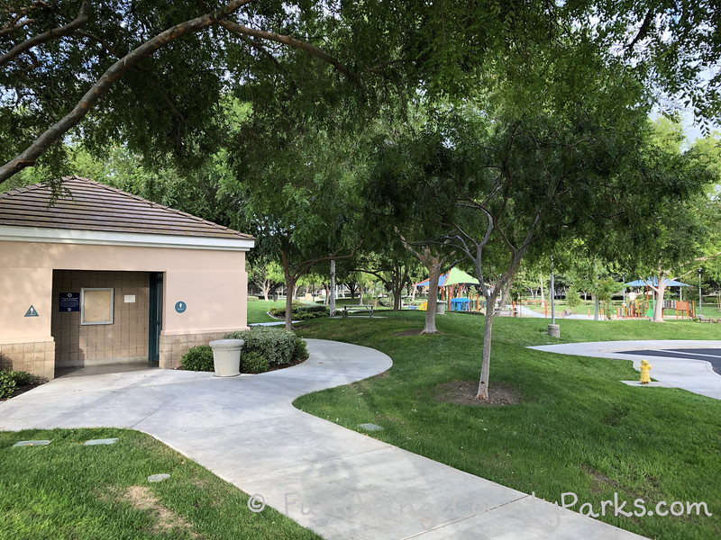 restroom building at Plaza Park in Irvine with a perspective that shows how close the playground is through the trees.