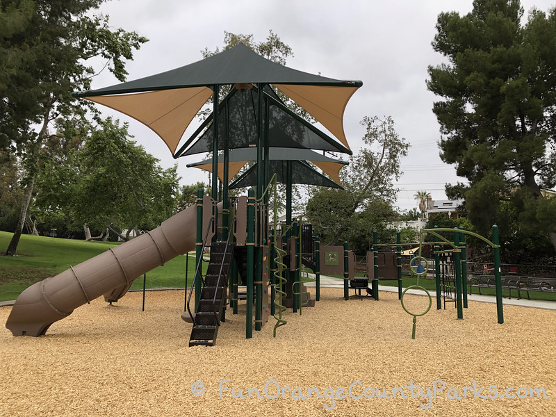 large playground with tan and green shade sails over the play structure on a bark surface with surrounding trees