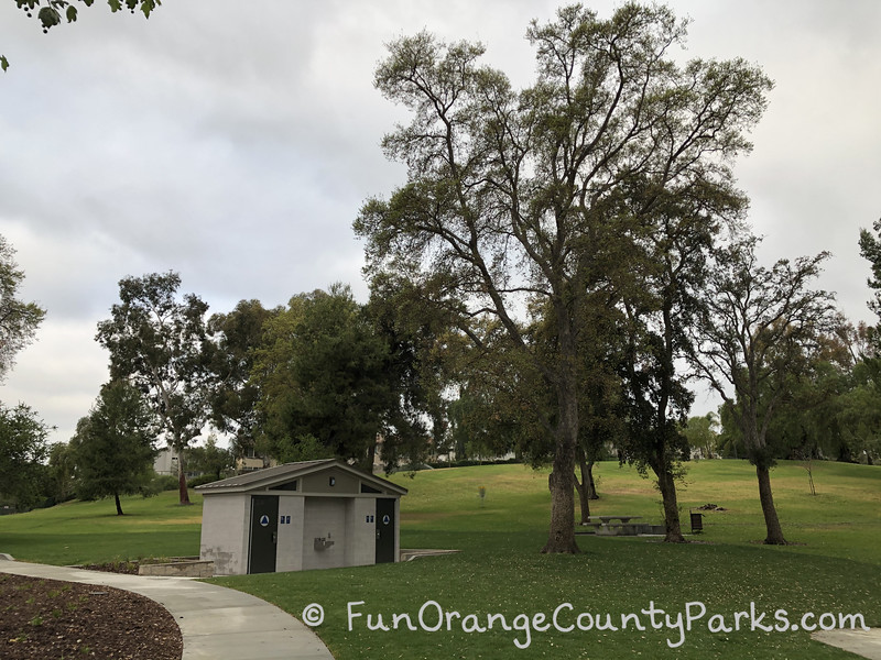 restroom building at Rolling Hills Park in Fullerton underneath tall trees against a cloudy sky
